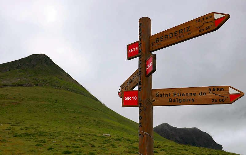 Wegweiser am Col de Buztanzelhay mit dem markanten, baskischen Schriftbild auf dem Pfosten.